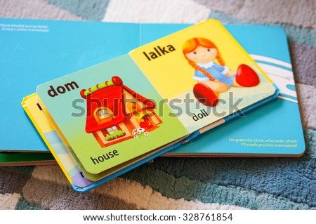 POZNAN, POLAND - JULY 14, 2015: Open baby book in Polish translated to English - stock photo
