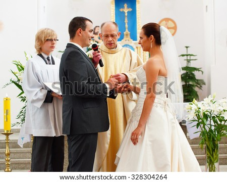 POZNAN, POLAND - 26 JUNE, 2012: Bride and groom by a priest at a traditional wedding ceremony in a church  - stock photo