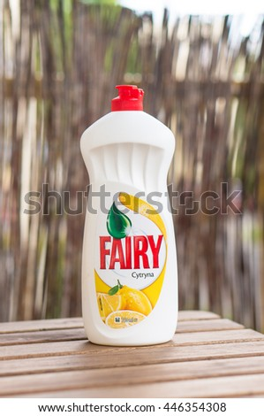 POZNAN, POLAND - JUNE 28, 2016: Fairy detergent with lemon aroma in a bottle standing on wooden table