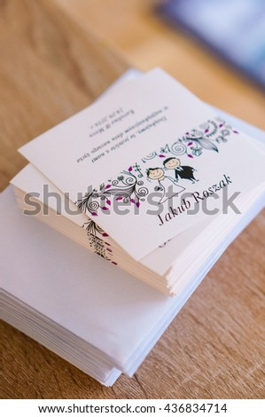 POZNAN, POLAND - JUNE 12, 2016: Stack of wedding invitation cards with names on wooden table - stock photo