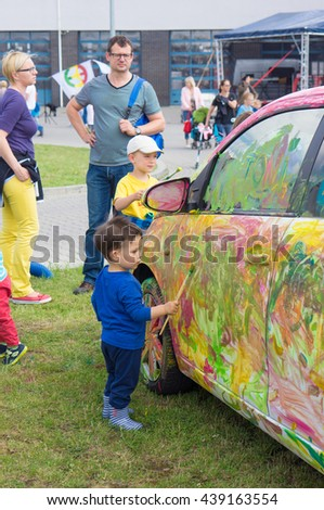 POZNAN, POLAND - JUNE 18, 2016: Unidentified boy painting a car with water color on a child event organized by the local fire department