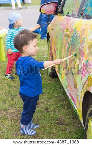 POZNAN, POLAND - JUNE 18, 2016: Unidentified children painting a car with water color on the Bezpieczne Wakacje child event organized by the local fire department