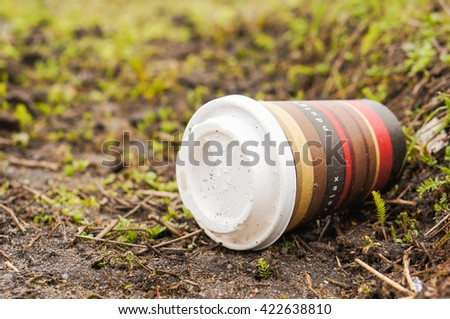 POZNAN, POLAND - MARCH 23, 2016: Paper cup with coffee lying on green grass affecting the environment - stock photo