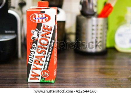 POZNAN, POLAND - MARCH 22, 2016: Polish Mlekovita Wypasione full milk in a paper box on wooden table  - stock photo
