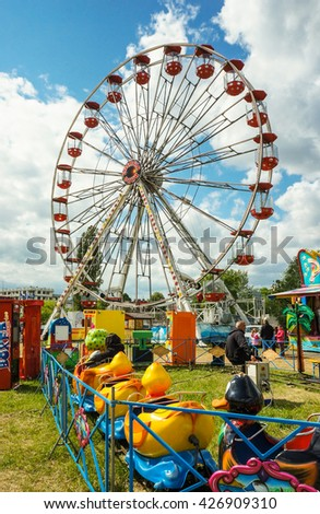POZNAN, POLAND - MAY 15, 2016: Ferris wheel and duck cart attraction on a luna park on a sunny day - stock photo