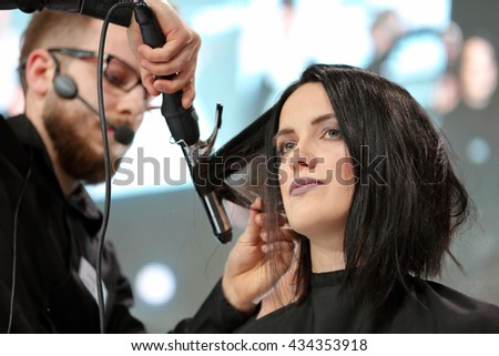 POZNAN, POLAND - MAY 07. 2016: Hairdresser arranging hairdo at The Look Beauty Vision Poznan 2016 on May 07 in Poznan, Poland.