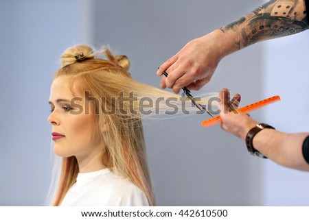 POZNAN, POLAND - MAY 07. 2016: Hairdresser trimming blond hair with scissors at The Look Beauty Vision Poznan 2016 on May 07 in Poznan, Poland.