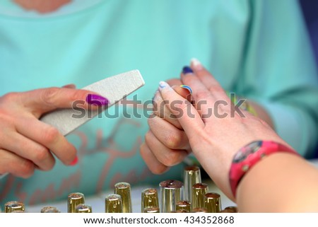 POZNAN, POLAND - MAY 07. 2016: Manicurist master makes manicure on young woman hand at The Look Beauty Vision Poznan 2016 on May 07 in Poznan, Poland.