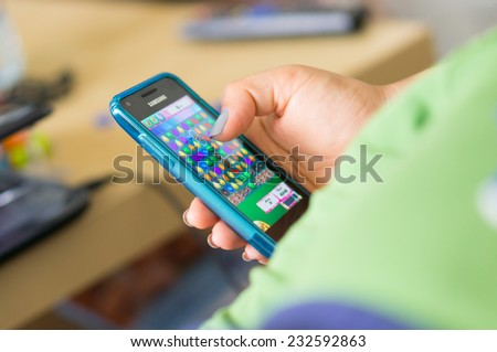 POZNAN, POLAND - MAY 08, 2014: Person playing Candy Crush Saga game on a smartphone