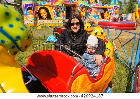 POZNAN, POLAND - MAY 15, 2016: Unidentified woman and child sitting in a duck cart attraction on a luna park on a sunny day