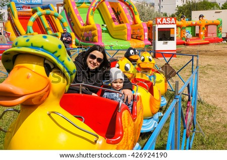 POZNAN, POLAND - MAY 15, 2016: Unidentified woman and child sitting in a duck cart attraction on a luna park on a sunny day - stock photo