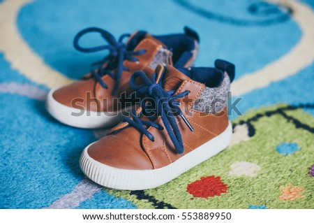 POZNAN, POLAND - NOVEMBER 13, 2016: Pair of brown Zara Baby leather child shoes on a carpet in soft focus