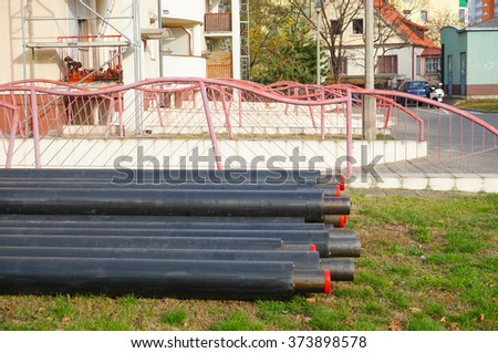 POZNAN, POLAND - NOVEMBER 01, 2015: Pile of plastic pipes by an apartment block - stock photo