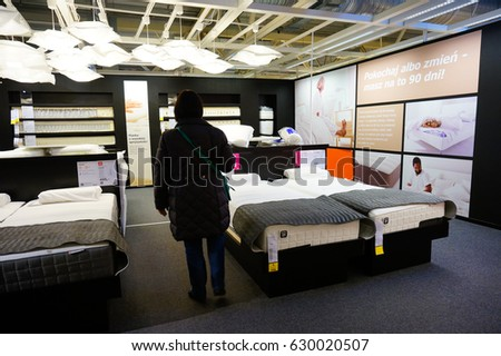 POZNAN, POLAND - NOVEMBER 24, 2013: Woman looking at beds in a Ikea furniture store