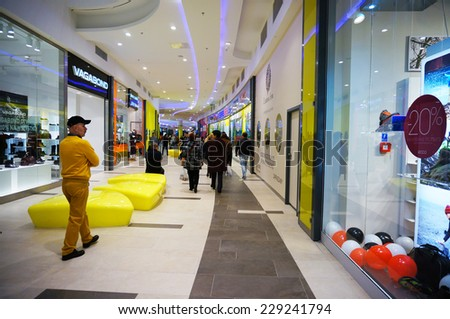 POZNAN, POLAND - OCTOBER 26, 2013: People passing stores in the Poznan City Center shopping mall - stock photo