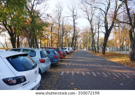 POZNAN, POLAND - OCTOBER 31, 2015: Row of parked cars by the Citadel park in the autumn season