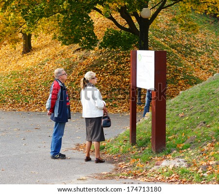 POZNAN, POLAND - OCTOBER 20, 2013: Senior couple looking at a information sign at the Citadel park