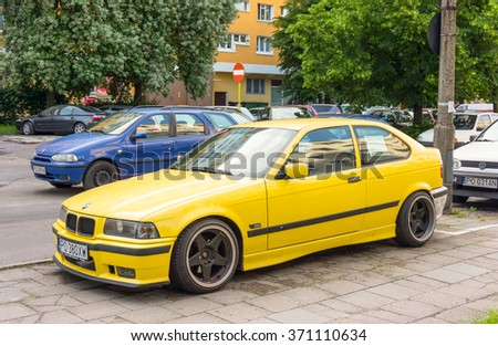 POZNAN, POLAND -  OCTOBER 10, 2014: Yellow BMW car for sale parked next to a sidewalk by apartment block