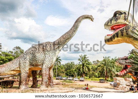 PRACHIN BURI, THAILAND - January 6, 2018 A model of a dinosaur zoo or a beautiful and ferocious dinosaur statue in nature with a bright sky.