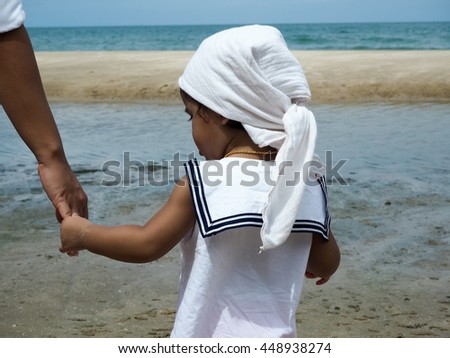 PRACHUAP KHIRI KHAN, THAILAND -JULY 2, A little thai girl is hold adult hand for walking to the sea at Hua Hin beach on July 2, 2016 in Prachuap Khiri Khan, Thailand - stock photo