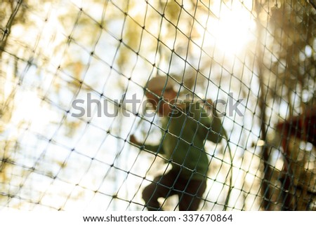 practice nets playground. a boy plays in the Playground shielded with a protective safety net. blurred background and blurred motion due to the concept - stock photo