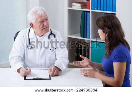 Practiced doctor talking with young female patient - stock photo