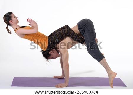 Practicing acro yoga exercises in group.Man and woman doing yoga exercises in studio on white background. - stock photo