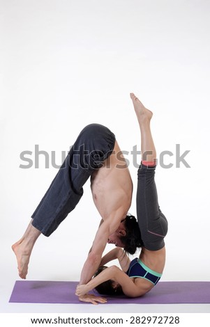 Practicing acro yoga exercises in group. People doing yoga exercises in studio on white background. - stock photo