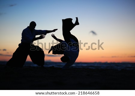 Practicing aikido technique, silhouettes of masters - stock photo