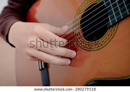 Practicing in playing guitar. Handsome young men playing guitar