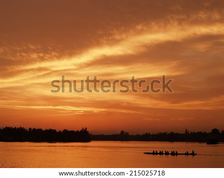 Practicing race boat under sunset sky / The practicing race boat silhouette in the river was under sunset golden sky