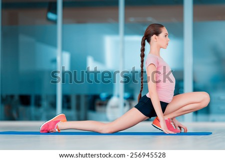 Practicing yoga. Beautiful teenage girl in sports clothing training yoga position on the mat in health club - stock photo