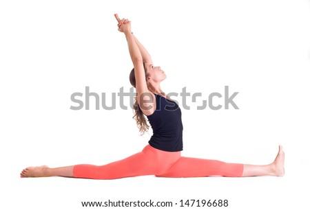 Practicing Yoga exercises. Young  woman doing  Yoga exercises in studio on white background.  Pose name: Monkey Pose - Hanumanasana  - stock photo