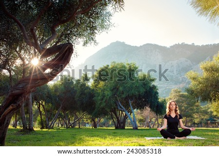 Practicing yoga in the morning, with trees, mountains and sun ray in the background. Attractive young woman sitting in lotus pose on the grass. Concept of calm and meditation. - stock photo