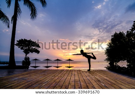practise yoga beside the swimming pool in the early morning silhouette - stock photo
