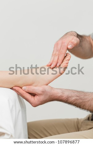 Practitioner holding the foot of a patient in a room