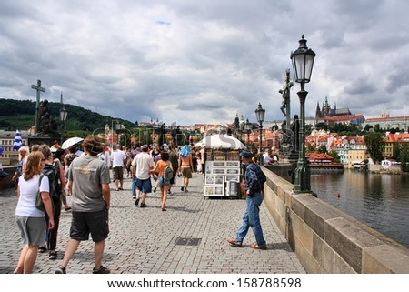 PRAGUE - AUGUST 3: People visit Charles' Bridge on August 3, 2008 in Prague, Czech Republic. Old Prague is a UNESCO World Heritage Site. Half of Czech tourism income is spent in Prague.