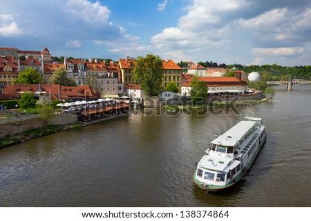 Prague buildings along Vltava river with cruise ship - stock photo