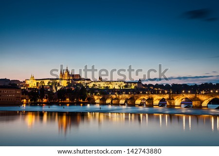 Prague caste and the Charles bridge evening reflection - stock photo