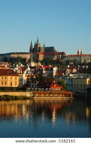 Prague Castle and St. Vitus Cathedral in the early morning sunlight, with reflections on the Vltava river