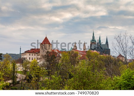 Prague Castle with the cathedral of St. Vitus on the hill with a beutiful frame of trees at the foreground. Spring time.