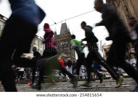 PRAGUE, CZECH REPUBLIC - APRIL 6, 2013: Athletes run past the Old Town Bridge Tower of the Charles Bridge during the Prague international marathon in Prague, Czech Republic. - stock photo