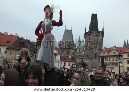 PRAGUE, CZECH REPUBLIC - APRIL 30, 2013: Participants of the costumed parade at the Witches Night carry a straw witch over the Charles Bridges in Prague, Czech Republic. - stock photo