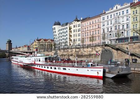 Prague, Czech Republic - April 22, 2015: Quay in the center of Prague. Boat on Vltava river near Juraskuv bridge - stock photo