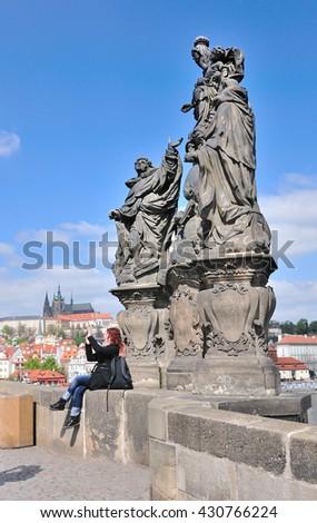 PRAGUE,CZECH REPUBLIC.- April 20,2016: Unidentified woman take a photograph with Statue on Charles Bridge and Prague Castle in background , Czech Republic.  - stock photo