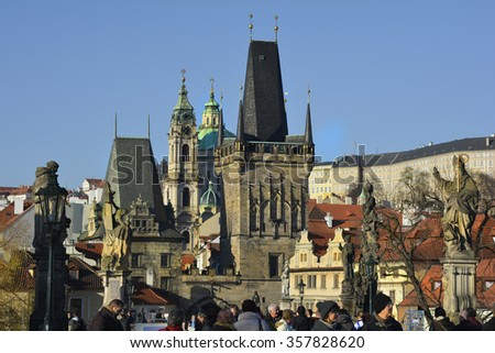 PRAGUE, CZECH REPUBLIC - DECEMBER 03: Sculpture on Charles bridge aka Karluv Most a preferred Tourist attraction,with view to Saint Nicholas church and church tower, on December 03, 2015 in Prague