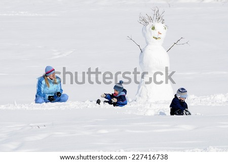 PRAGUE, CZECH REPUBLIC - FEBRUARY 24, 2013: Mother and her children play with snowman. - stock photo