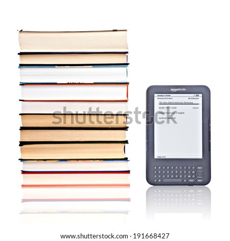 PRAGUE, CZECH REPUBLIC - FEBRUARY 5, 2011: Studio shot of 3rd generation reading device Amazon Kindle in comparison of pile of books.