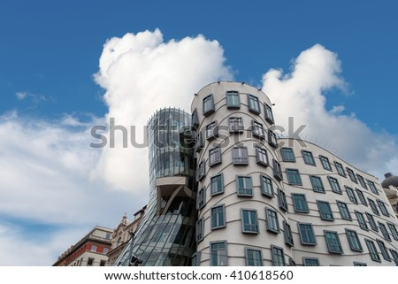 PRAGUE, CZECH REPUBLIC - JANUARY 2, 2016 : View of famous glass building with asymmetrical shape Dancing House, on cloudy blue sky background. - stock photo