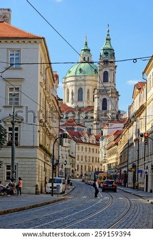 PRAGUE, CZECH REPUBLIC - JULY 3, 2014: Karmelitska street and the tall towers of St. Nicholas church in the background in Lesser town district. - stock photo